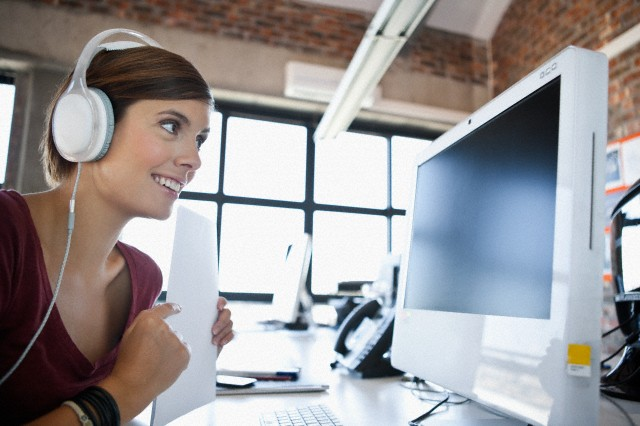 Young woman working on computer and listening to music in office